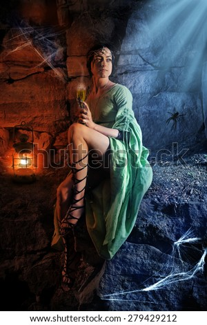 Beautiful elf princess is drinking a wine in the cave. - stock photo