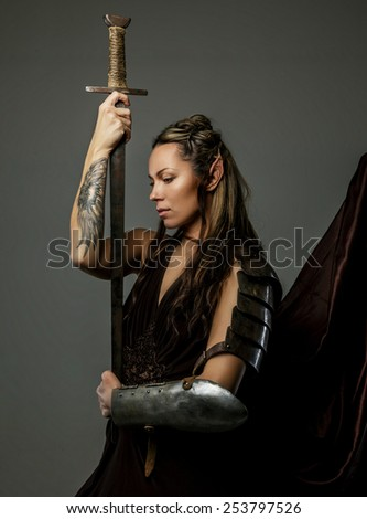 Beautiful elf woman with bow in her hand. Isolated on gray. - stock photo