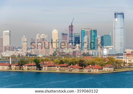 Beautiful Ellis Island with Jersey City background skyline from Liberty Island. - stock photo