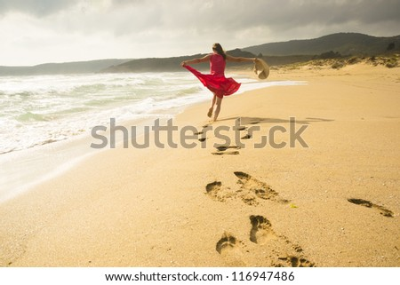 Beautiful energetic young woman running freely on the beach - stock photo