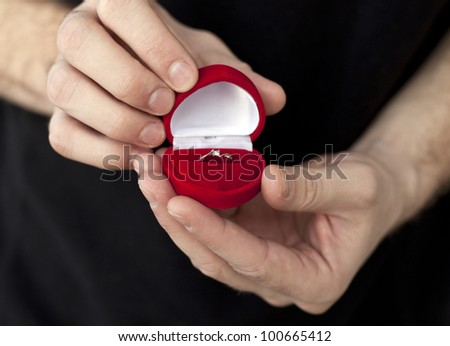 Beautiful engagement ring in red box in mans hands - stock photo