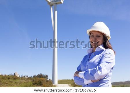 Beautiful engineer standing at wind farm - stock photo