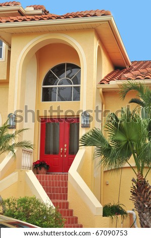 Beautiful entrance to a large, elegant three story home in lush Tropical Florida seated on a waterfront canal. Palms and bushes flank the tiled stairs leading to the double doorway. - stock photo