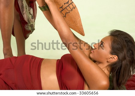 Beautiful ethnic female lies down on back under attack, struggling to push away wooden lance that she attacked with - stock photo