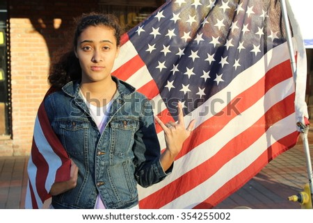 Beautiful ethnic teenage girl in front of a flag of the U. S. - stock photo