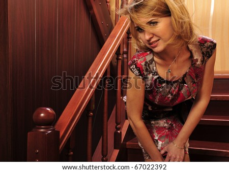 Beautiful European young woman standing on stairs and posing on camera before party starts - stock photo