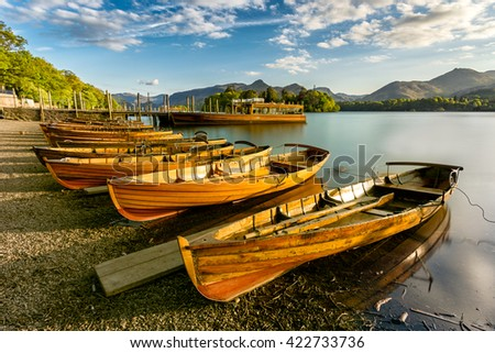 Beautiful evening golden light shining on row of rowing boats at Keswick Boat Launch in the English Lake District. - stock photo