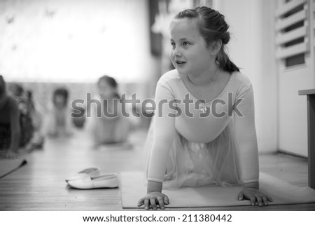 Beautiful excited girl doing gymnastic exercises; monochrome - stock photo