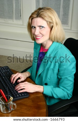 Beautiful executive business woman smiling and typing on her computer keyboard in the office.