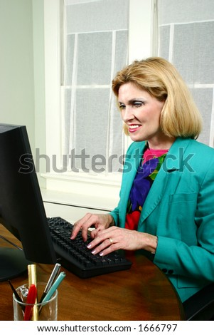 Beautiful executive business woman typing and smiling while working on her office computer. - stock photo