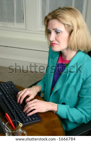 Beautiful executive business woman with a serious expression typing on an office computer. - stock photo