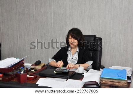 Beautiful executive woman working with documents in the office - stock photo