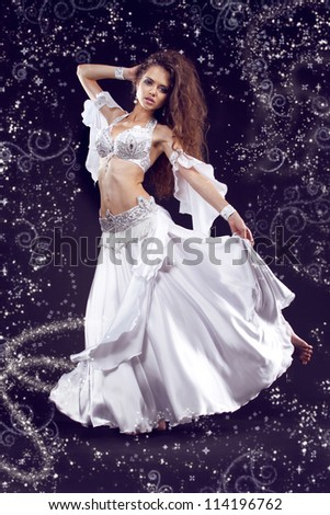 Beautiful exotic belly dancer woman in white costume, girl with smart fair hair