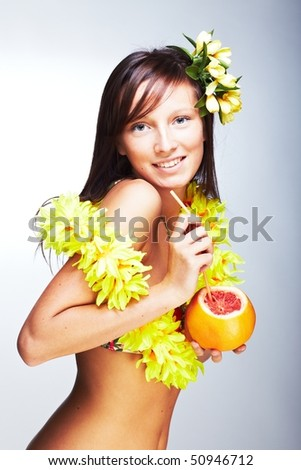 Beautiful exotic girl with Hawaiian accessories drinking grapefruit juice - stock photo