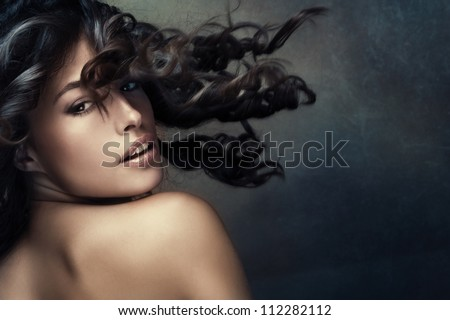 beautiful exotic tanned woman with long wavy hair in motion studio shot darker tones - stock photo