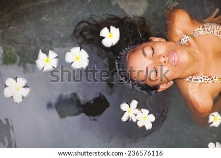 Beautiful exotic woman having bath in a luxury spa salon - stock photo
