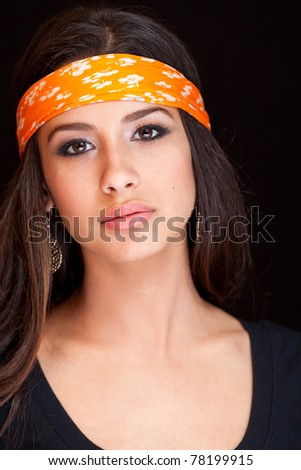 Beautiful exotic young woman wearing a bandana against a black background. - stock photo