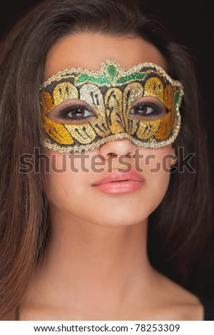Beautiful exotic young yoman wearing a masquerade mask against a black background. - stock photo