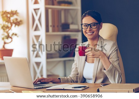 Beautiful expertise. Cheerful young beautiful businesswoman in glasses holding coffee cup and looking at camera with smile while sitting at her working place - stock photo