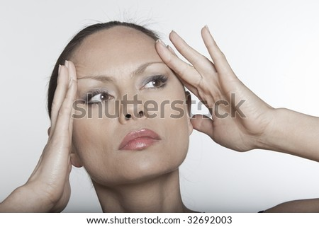 beautiful expressing woman portrait on siolated background massaging her face