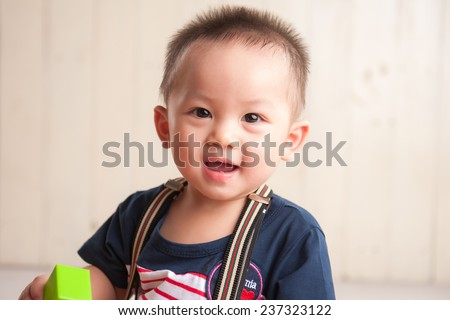 Beautiful expressive adorable happy cute laughing smiling asian baby infant face looking at camera. Closeup portrait of baby. - stock photo