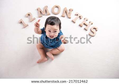 Beautiful expressive adorable happy cute laughing smiling baby infant face thumps up, isolated on white background. 12 months. age concept. - stock photo
