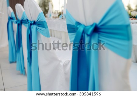 Beautiful fabric bow on the chair. Wedding restaurant for marriage. White decor for bride and groom. Colorful decoration for celebration. Beauty bridal interior - stock photo