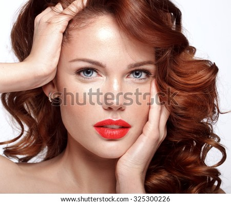 Beautiful face of a fashion model with blue eyes.Curly hair. Red lips. Studio portrait. - stock photo