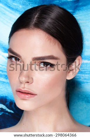 Beautiful face of a fashion model with professional make up. Art blue background.  - stock photo