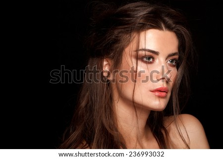 Beautiful face of a glamour woman with smoky eyes make up. Close up beauty portrait of young beautiful woman. Shooted on black background - stock photo