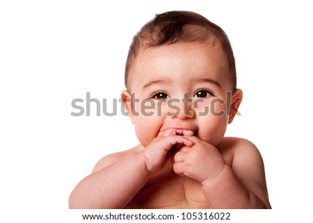 Beautiful Face of a happy cute baby infant with hands in mouth, isolated.