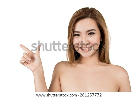 Beautiful face of young adult Asian woman pointing her finger in the air isolated on white background - stock photo