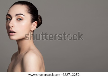 Beautiful face of young adult woman with clean fresh skin and bare shoulders on grey background. Brunette Spa Girl with perfect skin Portrait. Big blue eyes and passionate lips. - stock photo