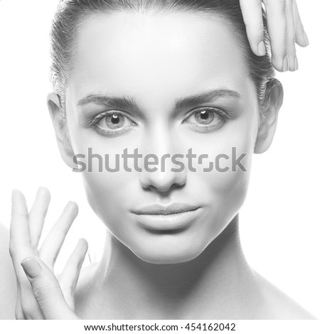 Beautiful face of young caucasian brunette woman with natural lips, make-up and blue eyes isolated on white. Touch her perfect skin. Studio portrait. Black and white - stock photo