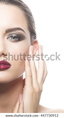 Beautiful face of young caucasian brunette woman with red glossy lips, intensive make-up, perfect skin and blue eyes isolated on white touch her skin. Studio portrait.  - stock photo
