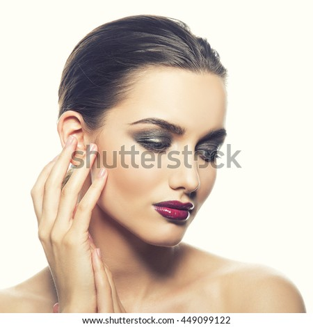Beautiful face of young caucasian brunette woman with red glossy lips, intensive make-up, perfect skin and blue eyes isolated on white touch her skin. Studio portrait. Toned - stock photo