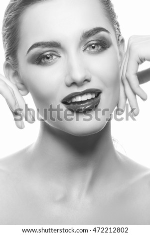 Beautiful face of young caucasian brunette woman with red glossy lips, intensive make-up, perfect skin and blue eyes isolated on white touch her skin. Studio portrait. Black and white