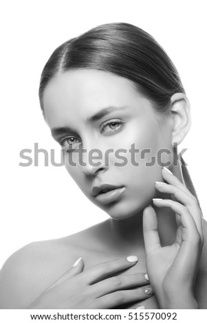 Beautiful face of young caucasian girl with natural make-up, perfect skin and green eyes touch her skin isolated on white background. Studio portrait. Black and white