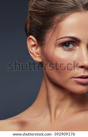 Beautiful face of young caucasian girl with natural make-up, perfect skin isolated on dark grey background. Studio portrait. Toned - stock photo