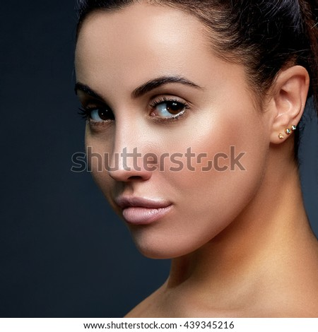 Beautiful face of young caucasian girl with natural make-up, perfect skin isolated on dark grey background. Studio portrait.