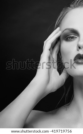 Beautiful face of young caucasian woman with red lips, perfect skin and green eyes isolated on black. Studio portrait. Black and white - stock photo