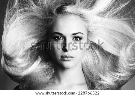 Beautiful Face of Young Woman.Blond girl.close-up.Art monochrome portrait.Beautiful healthy hair.Beauty salon.flying hair - stock photo