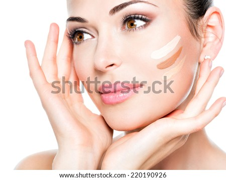 Beautiful face of  young woman with cosmetic foundation on a skin.   Beauty treatment concept - stock photo