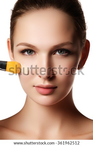 Beautiful face of young woman with cosmetic foundation on a skin. Beauty treatment concept. Makeup artist applying liquid tonal foundation on the face of the woman. Closeup photo of cheek - stock photo