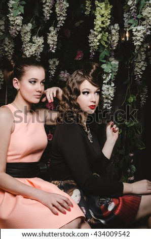 Beautiful faces of young caucasian pair of girls with evening make up, fashion clothes dress in blooming magic forest. Fashionable sexy couple of pretty women. Floral background in studio photo.