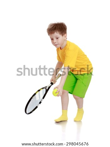 Beautiful fair-haired little boy in a yellow shirt, green shorts playing tennis , he's holding a racket which will supply the feed-Isolated on white - stock photo