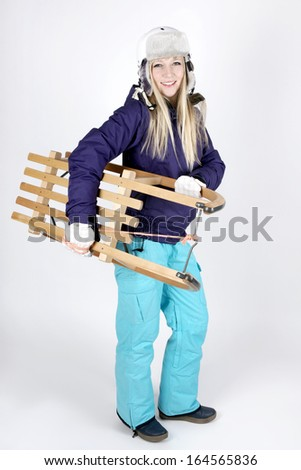 Beautiful fair haired young woman with a sleigh - stock photo