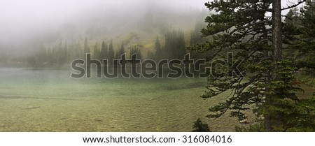 Beautiful Fairy Lake, cloaked in chilly fog.  Located in Montana's Bridger Range, in Gallatin National Forest, near Bozeman and Yellowstone. - stock photo