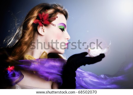 beautiful fairy sending a kiss to a little bird on her palm, profile,  studio shot - stock photo