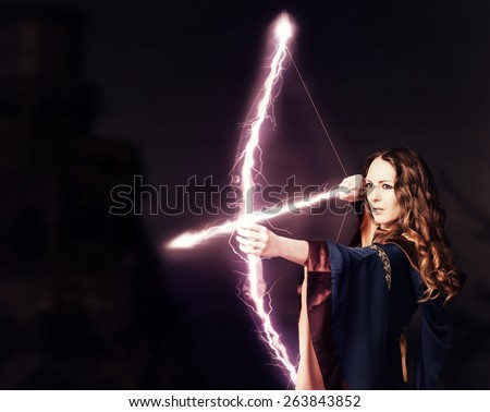 Beautiful fairy woman archer with a magic bow at night on dark background - stock photo
